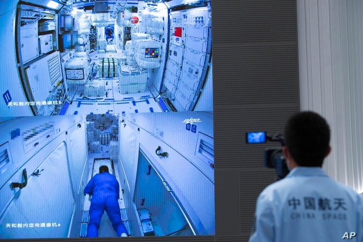 In this photo released by Xinhua News Agency, a worker monitors screens showing the interior of the Tianhe space station module…