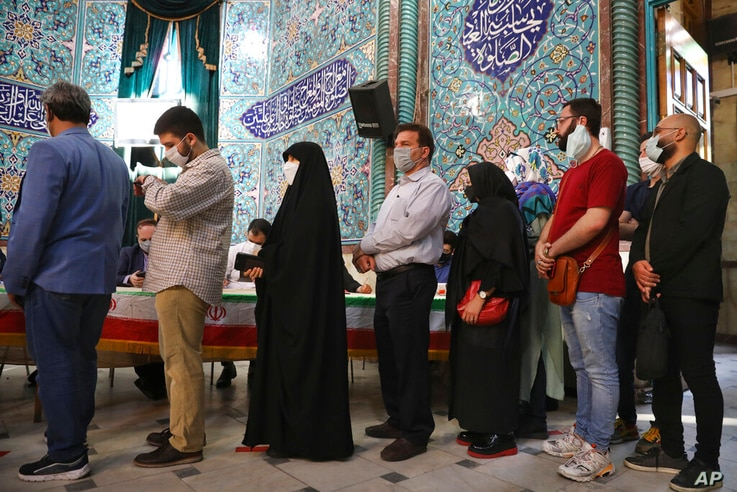 Voters queue at a polling station during the presidential elections in Tehran, Iran, Friday, June 18, 2021. Iranians voted...