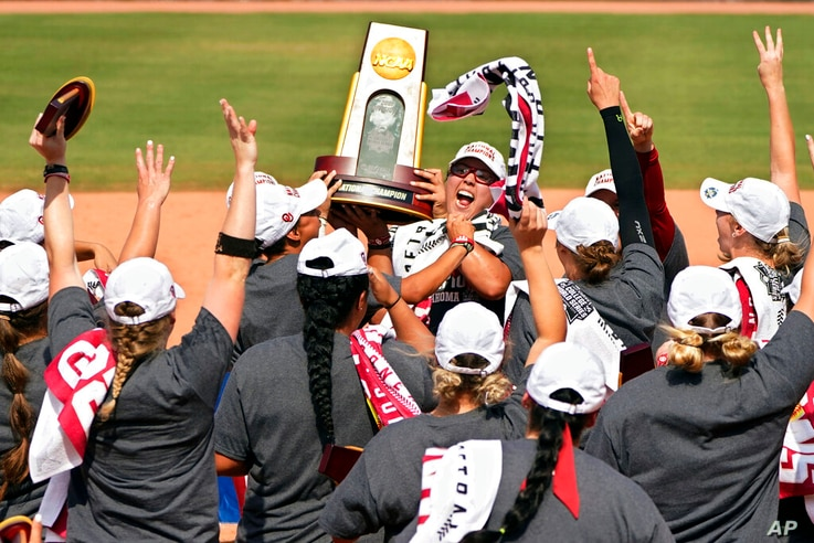 FILE - In this Thursday, June 10, 2021, file photo, Oklahoma players celebrate with the trophy after defeating Florida State in…