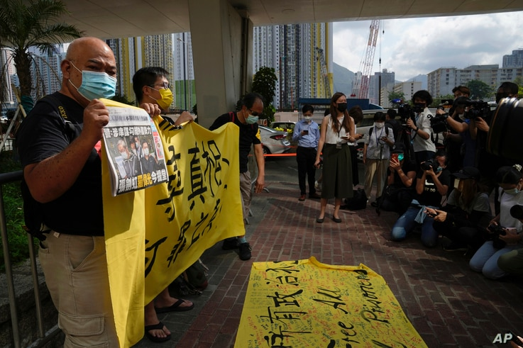 Pro-democracy activists holding a copy of Apple Daily newspaper and banner protest outside a court in Hong Kong, Saturday, June 19, 2021, to demand to release political prisoners.