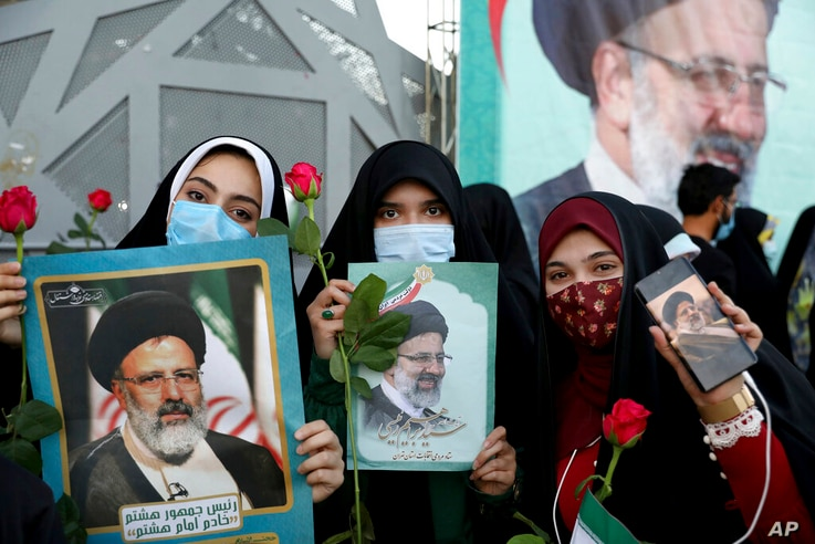 Supporters of Iranian president-elect Ebrahim Raisi celebrate after he won the presidential election in Tehran, Iran, Saturday,…