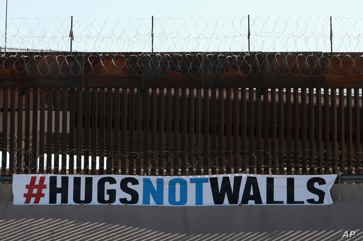 """A """"#HUGS NOT WALLS"""" banner is displayed along the border wall as part of 8th annual event on the Rio Grande, in Ciudad Juarez, Mexico, Saturday, June 19, 2021."""