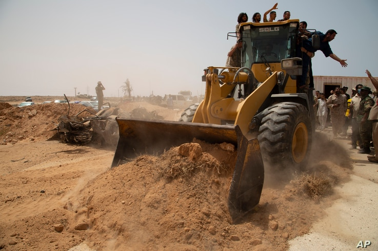 A bulldozer pushes earth to during a ceremony to reopen the road between the cities of Misrata and Sirte Sunday, June 20, 2021…