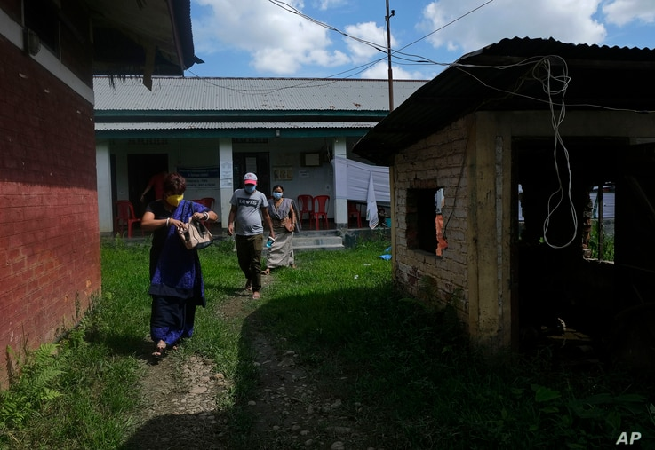 People leave a vaccination center after receiving the COVID-19 vaccine in Imphal, India, June 21, 2021.