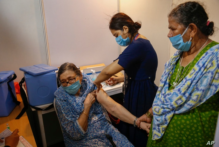 An elderly woman, left, holds the arm of her domestic helper as she receives Covishield vaccine against the coronavirus.