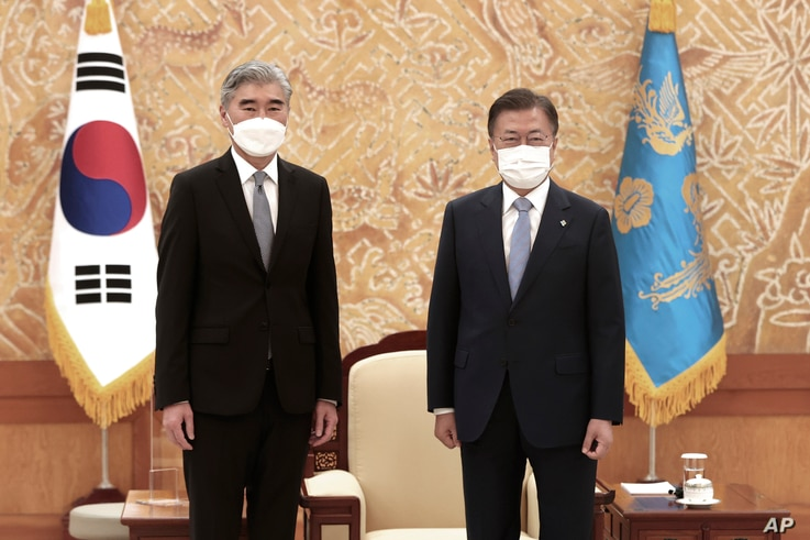 South Korean President Moon Jae-in, right, and U.S. Special Representative for North Korea, Sung Kim, pose for photos.