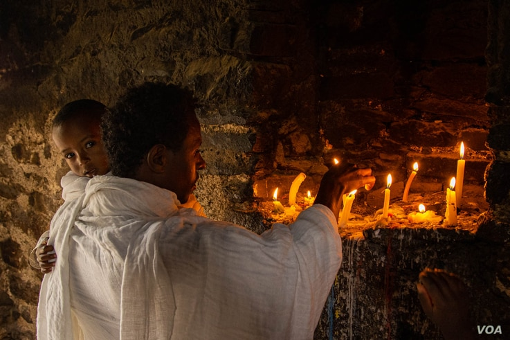 A father and his son go to the oldest church in Ethiopia to be blessed, in Axum, Ethiopia, June 13, 2021. (Yan Boechat/VOA)