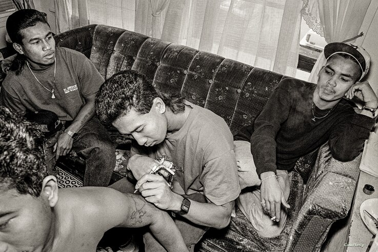 Cambodian Gino paints a gel tattoo on the arm of one of his friends in an apartment at a public housing building in Uptown, Chicago, 1990s. (Photo: Stuart Isett)
