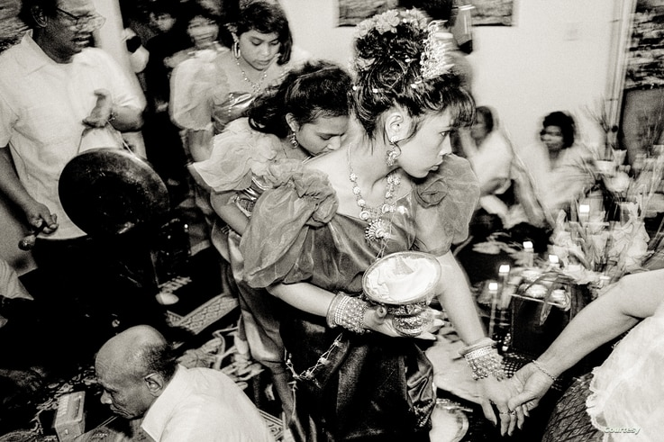 At an apartment in a public housing building on Chicago's north side, it's joy and trepidation at a traditional Cambodian wedding ceremony in the early 1990s. (Photo: Stuart Isett)