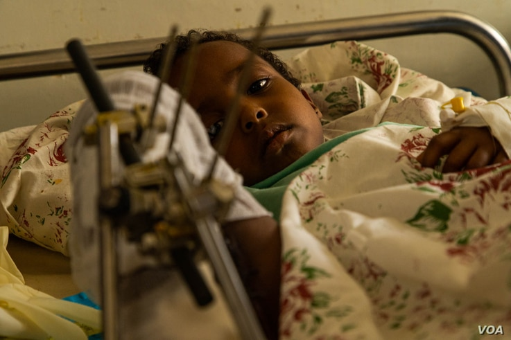 Samwarit, 4, lies on her hospital bed recovering from knife wounds in her leg and a gunshot in her hand, according to her father, in Mekelle, Ethiopia, June 4, 2021. (Yan Boechat/VOA)