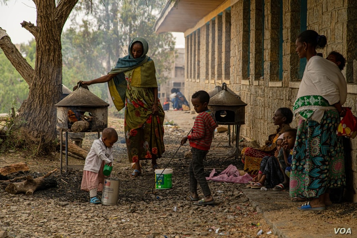 Families of refugees prepare injera, a traditional Ethiopian food, in the yard of one of many schools in Mekelle, Ethiopia, that are now camps for displaced families, June 3, 2021. (Yan Boechat/VOA)