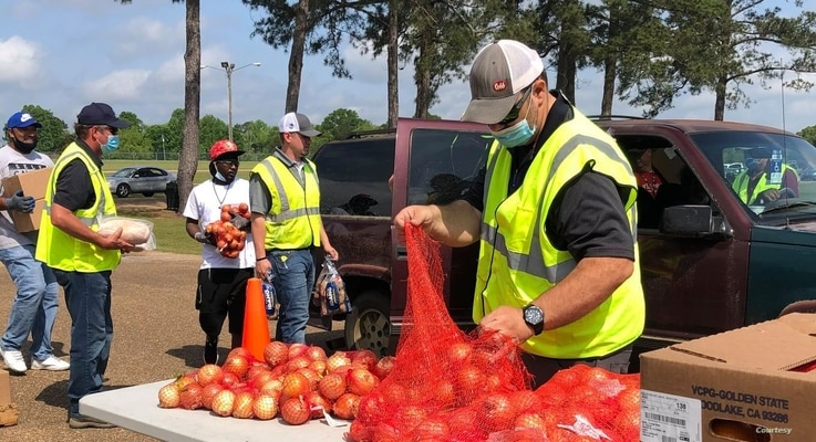 Volunteers with the Mississippi Food Network and the Tyson Foods company load vehicles with onions and other food in Forest, Mississippi.  The supplies were distributed to more than 300 families.