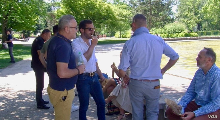 National Rally candidate Julien Odoul, second from left, visits with supporters in Montbeliard. (Lisa Bryant/VOA)