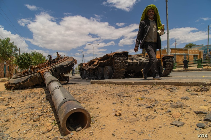 A man passes by a destroyed tank on the main street of Edaga Hamus, in the Tigray region, in Ethiopia, on June 5, 2021. (Yan Boechat/VOA)
