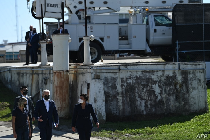 President Joe Biden (C) and Mayor of New Orleans LaToya Cantrell (R) take a tour of the Carrollton water treatment plant, in New Orleans, Louisiana, May 6, 2021.
