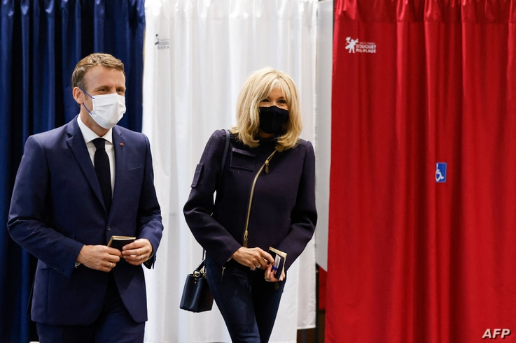 French President Emmanuel Macron (L) and his wife Brigitte Macron leave a polling station after casting their ballots in Le Touquet, in the second round of French regional elections, June 27, 2021.