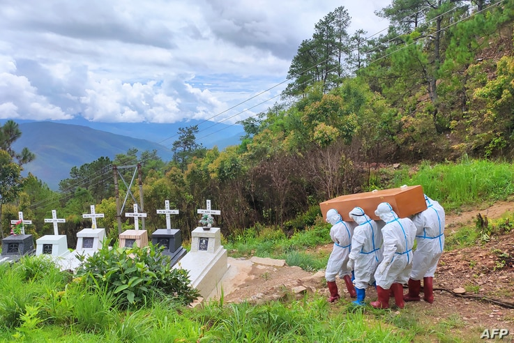 Health workers in protective suit carry a coffin of the body of a Covid-19 coronavirus patient during a burial at a cemetery in Falam township in western Myanmar's Chin state.
