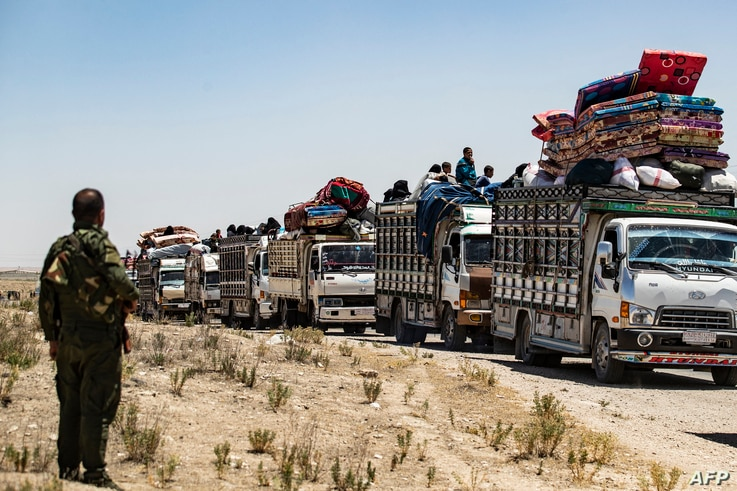 Syrian families sit in a truck after being released from the Kurdish-run Al-Hol camp, which holds relatives of suspected Islamic State (IS) group fighters, in the northeastern Syrian Hasakeh governorate.