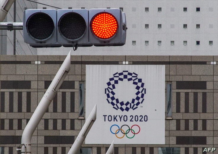 FILE - A red traffic light is seen on a street near the Tokyo Metropolitan Government Building displaying a banner of the Tokyo 2020 Olympics Games, in Tokyo, Japan, May 31, 2021.