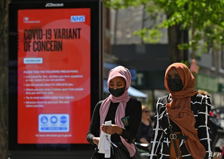 FILE - Pedestrians walk past a sign warning members of the public about a 'Coronavirus variant of concern,' in Hounslow, west London, Britain, June 1, 2021.