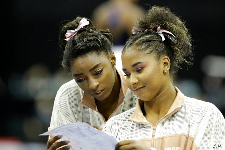 Simone Biles, left, and Jordan Chiles look over a rotation schedule during practice for the senior women's competition at the…