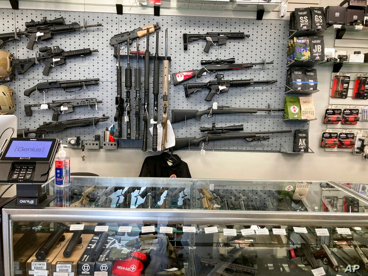 An assortment of rifles hang in a gun shop on Friday, Feb. 19, 2021, in Salem, Ore. So many people are buying guns in Oregon…
