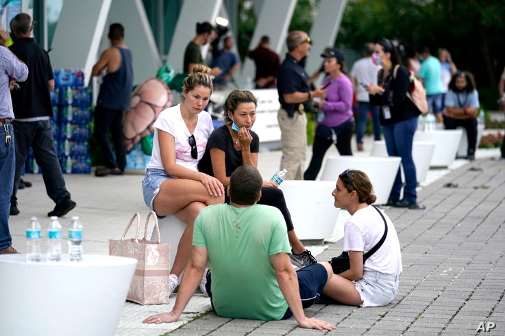 People wait for news at a family reunification center, after a wing of a 12-story beachfront condo building collapsed, Thursday.