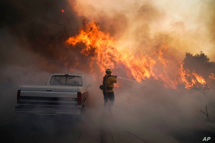 FILE - In this Oct. 26, 2020 file photo Firefighter Raymond Vasquez battles the Silverado Fire, in Irvine, Calif. U.S. wildfire…