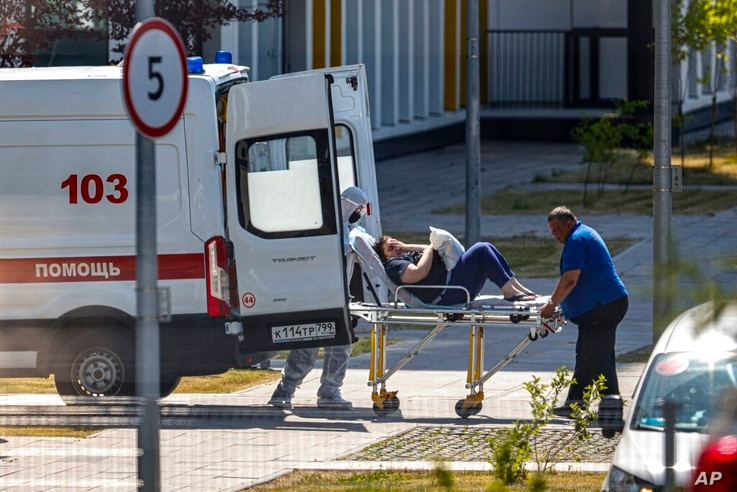 Medical workers carry a patient suspected of having coronavirus on a stretcher at a hospital in Kommunarka, outside Moscow,…