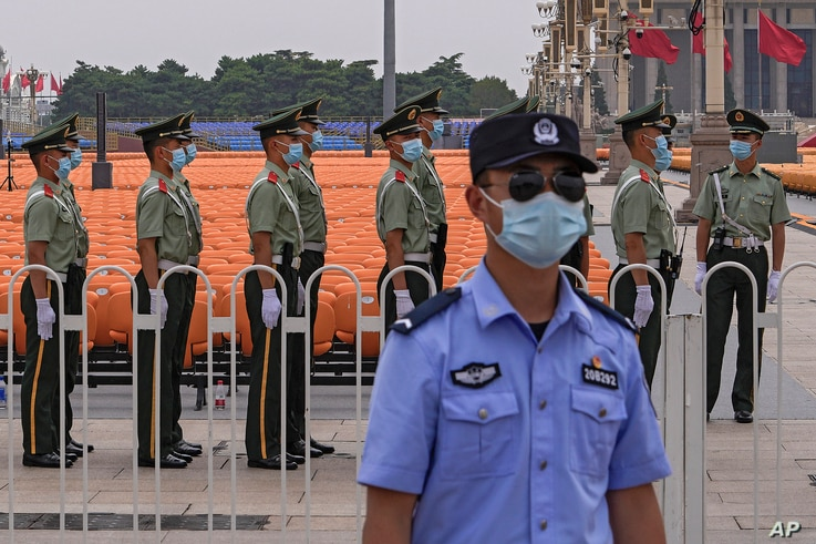 A police officer wearing a face mask to help curb the spread of the coronavirus stands guard.