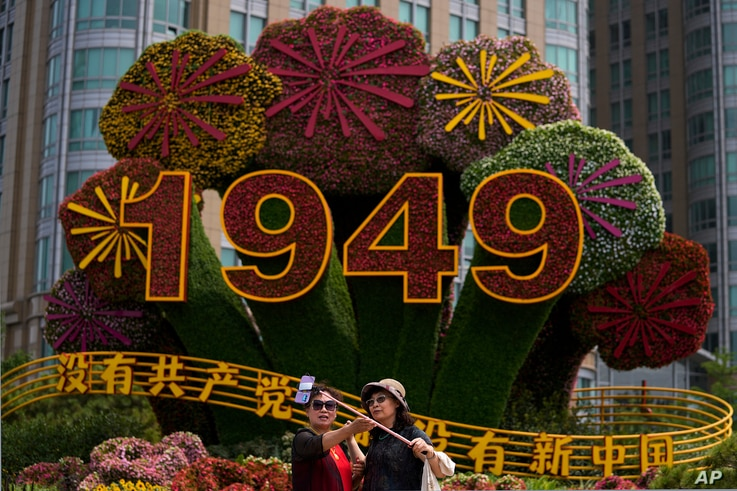 """Chinese women take a selfie with a floral decoration with the words """"Without the Communist Party, There would be no new China."""
