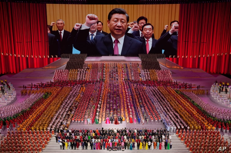 Chinese President Xi Jinping is seen leading other top officials pledging their vows to the party on screen during a gala show.