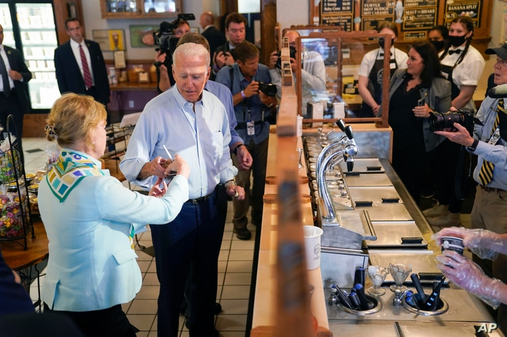 President Joe Biden hands ice cream to Sen. Tammy Baldwin, D-Wis., during a stop at The Pearl Ice Cream Parlor Tuesday, June 29…
