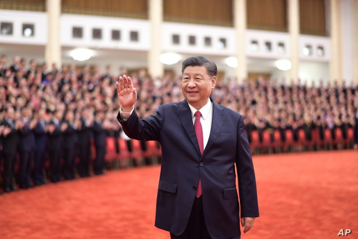 In this photo released by the Xinhua News Agency, Chinese President Xi Jinping is waving his hand.