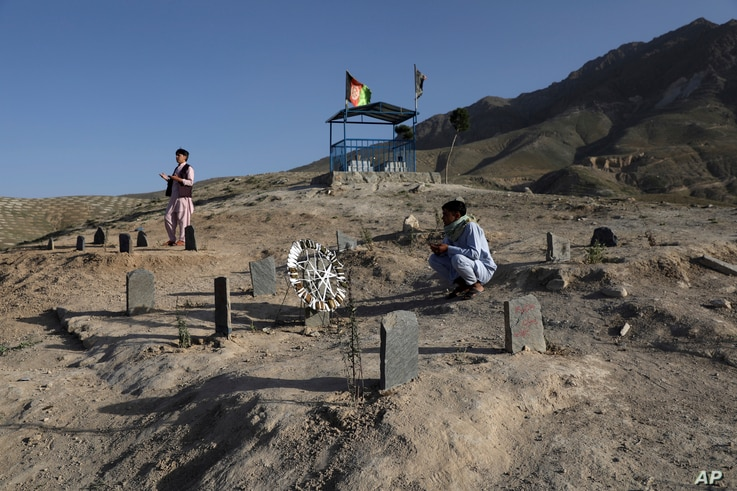 FILE - Men pray near the graves of their relatives killed in bombings near Syed Al-Shahada School in May, at a cemetery on the outskirts of Kabul, Afghanistan, June 2, 2021.