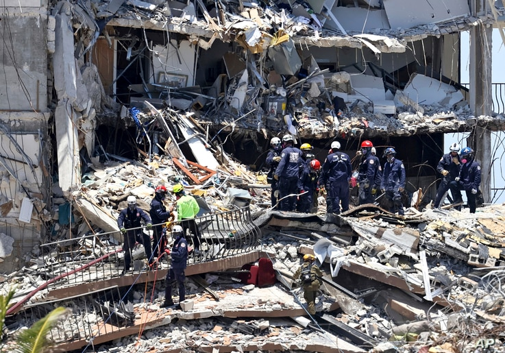 Search and rescue personnel search for survivors in the rubble at the Champlain Towers South in Surfside, Florida, June 27, 2021. (David Santiago/Miami Herald via AP)