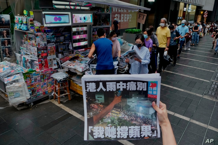A woman takes a photo from the latest edition of Apple Daily as people line up to buy the newspaper in Hong Kong.