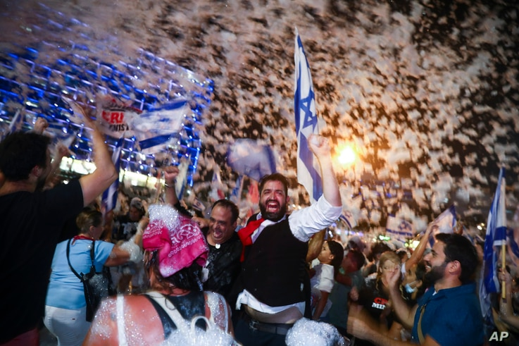 People celebrate the swearing-in of the a new government, in Tel Aviv, Israel, June 13, 2021.