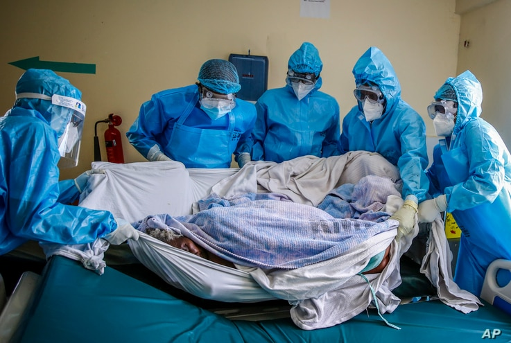 FILE - A medical team rolls a coronavirus patient from a bed onto a stretcher in the COVID-19 intensive care unit at Kenyatta National Hospital, in Nairobi, Kenya, April 14, 2021.