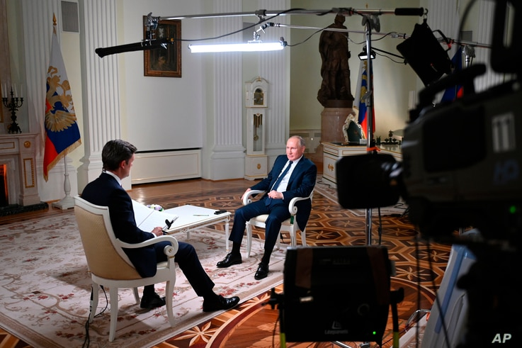 Russian President Vladimir Putin speaks to NBC News journalist Keir Simmons, back to a camera, in an interview aired on June 14, 2021.