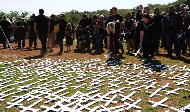 FILE - People place crosses, representing white farmers killed in South Africa, at a ceremony at the Vorrtrekker Monument in Pretoria, Oct. 30, 2017.