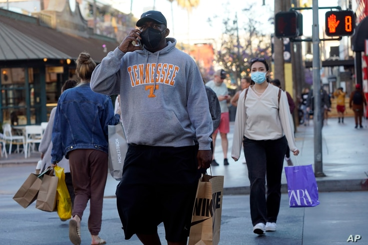 FILE - Shoppers wearing masks amid the COVID-19 pandemic cross a street on The Promenade in Santa Monica, California, June 9, 2021.