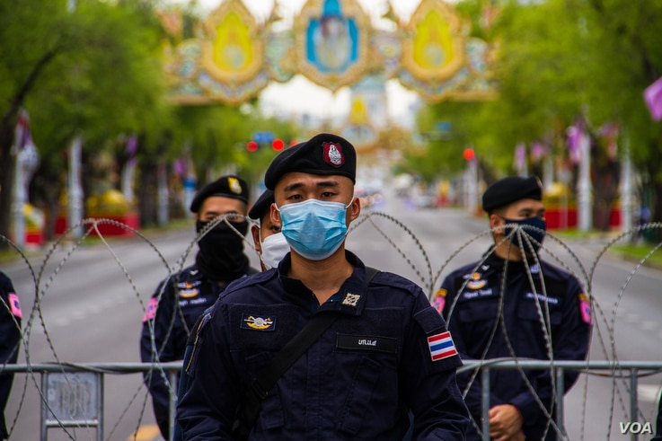 Thai police officer beside a barricaded road during anti-government protests, Bangkok, Thailand