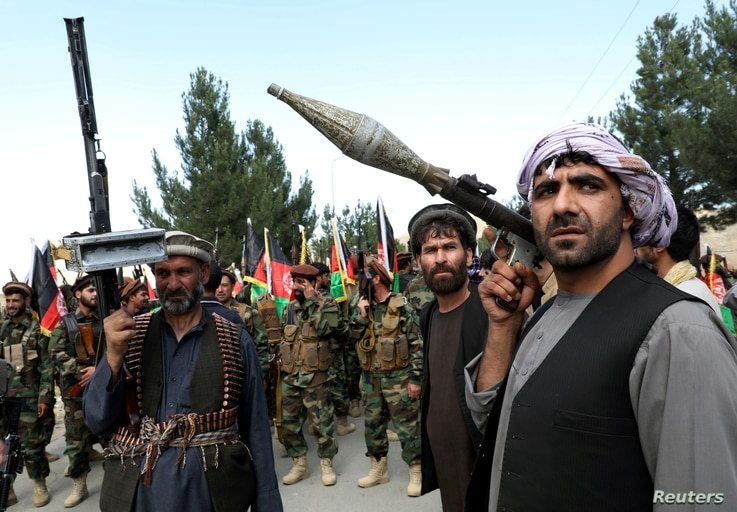 Armed men attend a gathering to announce their support for Afghan security forces and that they are ready to fight against the Taliban, on the outskirts of Kabul, June 23, 2021.