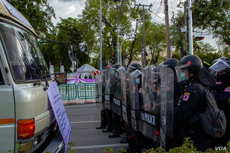 Activists threaten to drive towards riot police during heated protests outside Government House, Bangkok Thailand.