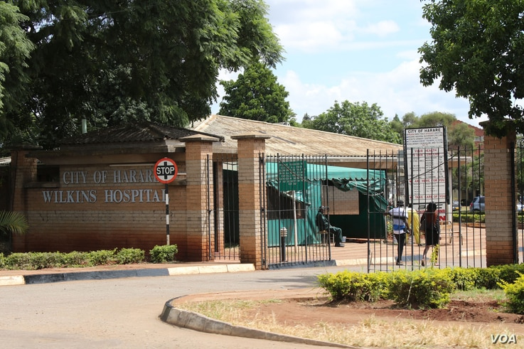People walk through the entrance gate of Wilkins Hospital in Harare, Zimbabwe's main COVID-19 inoculation center until vaccine shortages began in May of 2021. (Columbus Mavhunga/VOA)