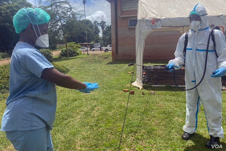 A health worker disinfects a colleague at Wilkins Hospital in February of 2021 when COVID-19 jabs there were still available. (Columbus Mavhunga/VOA)