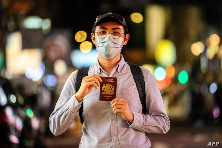 In this photo taken in Hong Kong on June 3, 2020, Reese Tan, a 25-year old tutor, poses with his British National (Overseas),…