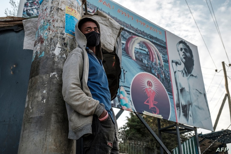 A young man stands in front of a sign of the Tigray People's Liberation Front (TPLF) party depicting the figure of former Prime…