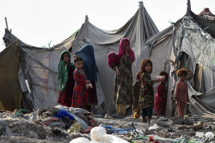 Children of Afghan refugees play outside tents in Afghan Basti area on the outskirts of Lahore on June 19, 2021 on the eve of…